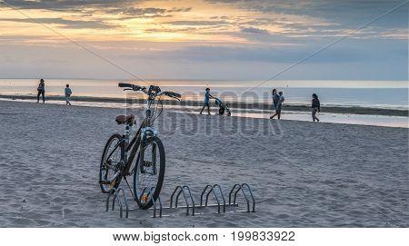 JURMALA, LATVIA - AUGUST 09, 2017: Bicycle at sandy beach of Jurmala - famous public domain resort in Latvia, Europe