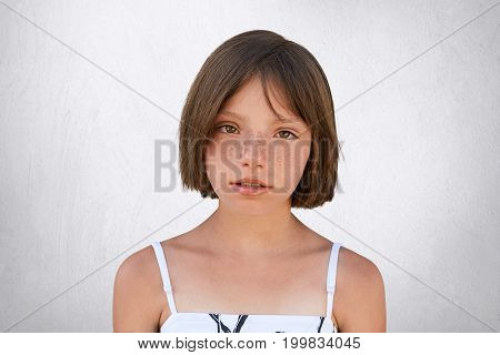 Serious Freckled Girl With Bobbed Hair And Dark Eyes Looking Directly Into Camera, Isolated Over Whi