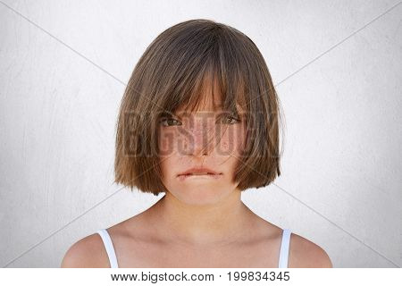 Upset Little Girl Having Quarrel With Her Parents, Looking Innocently Into Camera While Curving Her