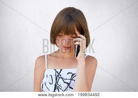 Small Child Communicating Over Smart Phone With Her Parents While Looking Down. Pretty Girl With Sho