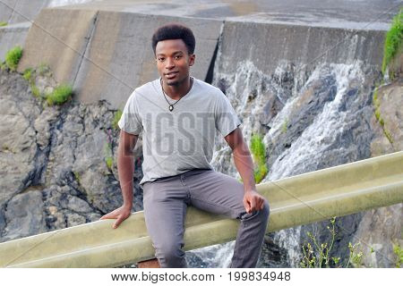 young man portrait t-shirt handsome person male outside near river water fall concrete barrage