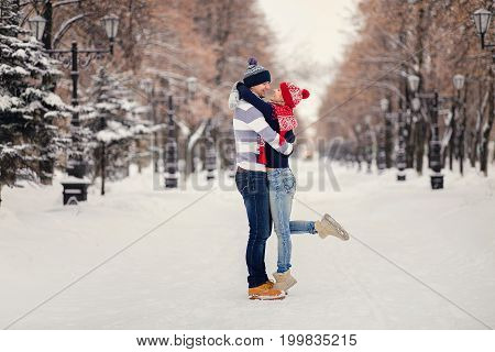 Young Couple Hugging And Kissing In The Park In Winter