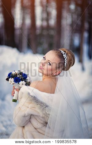 bride posing in the winter forest in a fur coat. Wedding photo session in a snowy Park.