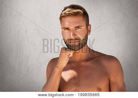 Serious Man With Bristle, Dark Attractive Eyes, Stylish Hairdo Standing Topless While Keeping His Ha