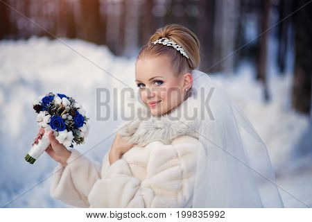 Beautiful bride in the winter forest. Bright winter wedding photo.