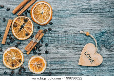Grains of coffee cinnamon and dried orange on a blue wooden background. A wooden heart with a word of love on a blue background.