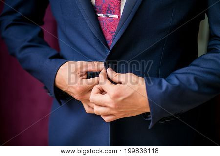 Business Man Button His Jacket On Purple Background
