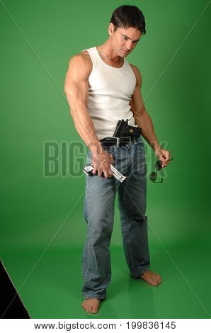 The sexy man is holding on to a pistol