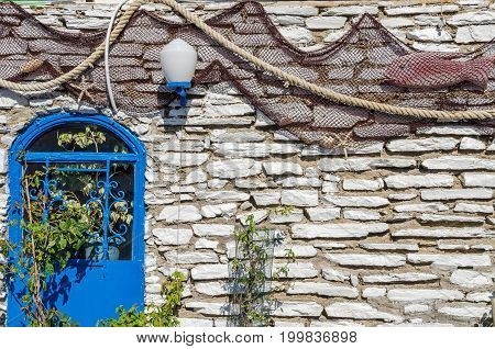 A typical decoration of the mediterranean restaurant with the blue fake door plants and fishing net which is common in Greece and Turkey.