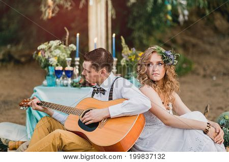 Romantic Couple Sitting Outdoors At Sunset With The Man Playing The Guitar. On The Background Is Dec
