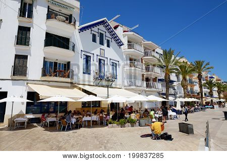 SITGES SPAIN - MAY 23: The tourists enjoiying their vacation in outdoor restaurant on May 23 2015 in Sitges Spain. Up to 60 mln tourists is expected to visit Spain in year 2015.