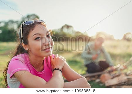 Tourist young woman sitting in the camp. In the background a blurred man chopping wood