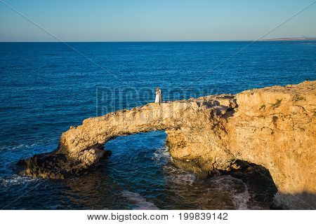 beautiful gorgeous blonde bride and stylish groom kissing on rocks, on the background of a sea, wedding ceremony on cyprus