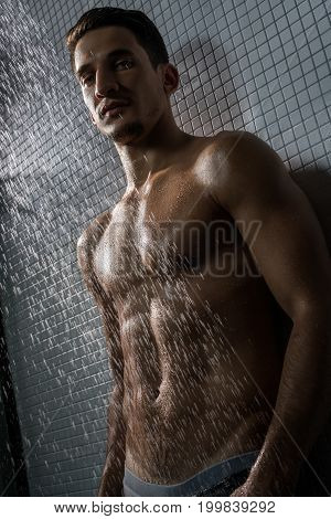 Young handsome muscular shirtless man shot in shower against gray tile wall