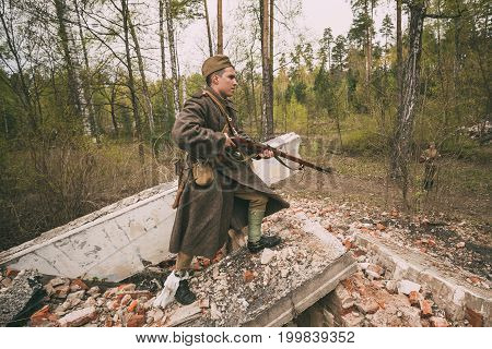 Pribor, Belarus - April 24, 2016: Re-enactor Dressed As Soviet Russian Red Army Infantry Soldier Of World War II Is Performing Mopping-up Operation With Rifle Along Rubble Of Building