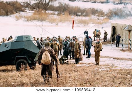 Rogachev, Belarus - February 25, 2017: Re-enactor Dressed As Soviet Russian Red Army Infantry Soldier Of World War Ii Goes To A Group Of Re-enactors Standing Near The Soviet Armored Car.