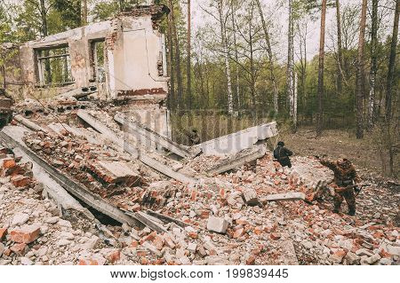 Pribor, Belarus - April 24, 2016: Re-enactors Dressed As Russian Soviet Red Army Soldiers Of World War II Performing Mopping-up Operation Among Wreckage Of Destroyed Building.