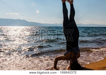 Young Woman Doing Handstand on the Sand at the Beach