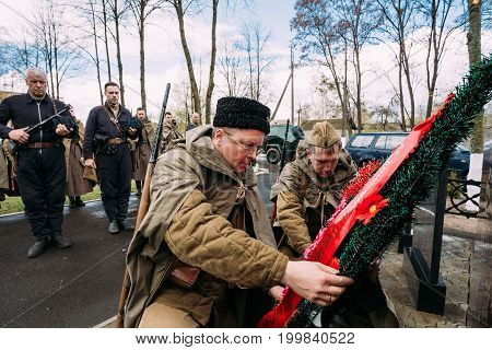 Pribor, Belarus - April 23, 2016: Unidentified Re-enactors Dressed As Russian Soviet Infantry Soldiers Of World War II Laying A Wreath At Common Grave Monument In Memory Of Fallen In Great Patriotic War.