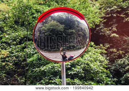 In road safety convex mirror reflecting Cycling biker. The concept of road safety for travelers bicyclists and drivers of scooters
