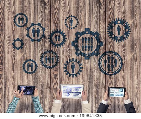 Group of three people with devices in hands working together as symbol of networking and communication