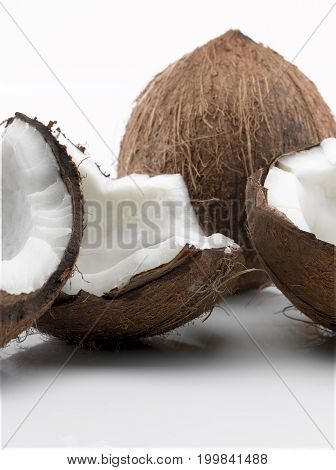 One Coconut Broken into Three Pieces with One Whole Coconut in Background