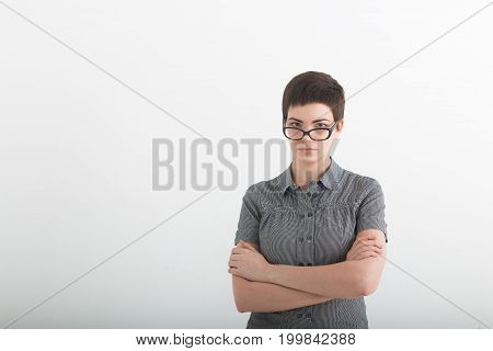 Confident business expert. Beautiful young woman in smart casual wear keeping arms crossed and looking serious while standing against grey background.