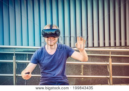 Young Man Enjoying Virtual Reality Glasses Headset Or 3D Spectacles On Urban Background Outdoors. Te