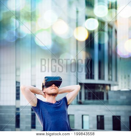 Young Man Enjoying Virtual Reality Glasses Headset Or 3D Spectacles Looking Up And Standing Against