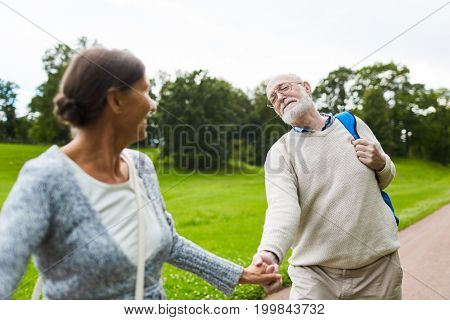 Aged woman pulling her husband by hand during trip while he is reluctant to go further