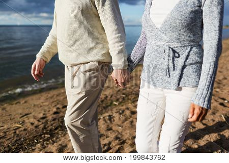 Aged couple holding by hands during walk on sandy beach in the evening