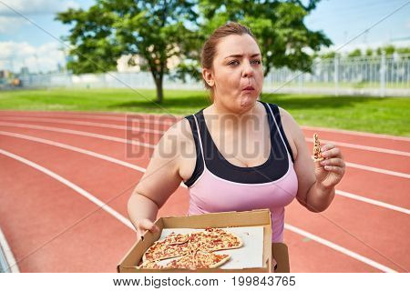 Chubby female in activewear eating pizza on the move on stadium