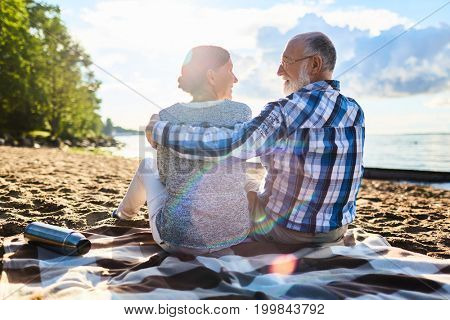 Affectionate seniors enjoying rest on sandy beach on sunny day