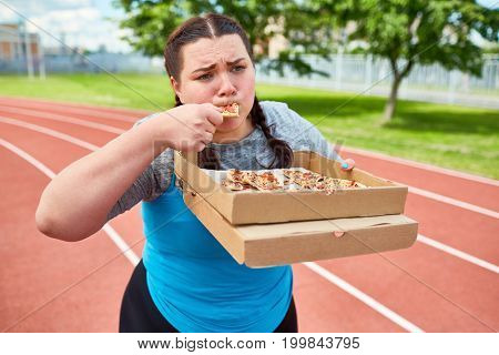 Plump female eating takeout pizza from box while walking down racetrack