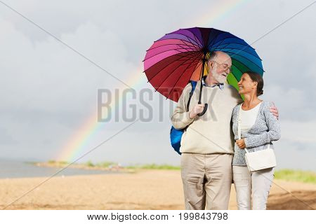 Amorous couple of pensioners looking at one another while standing under umbrella against rainbow and stormy sky