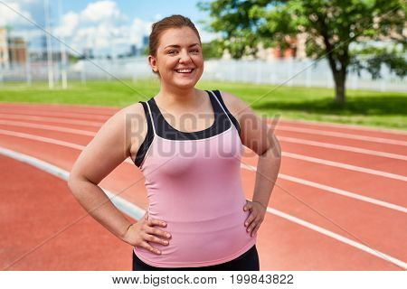 Happy young overweight female in activewear having training on stadium