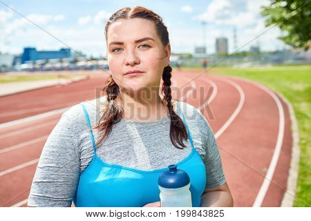 Young plump woman with pigtails standing on stadium and having break after workout