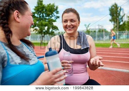 Friendly young women with bottles of water talking while having rest in the middle of workout on stadium