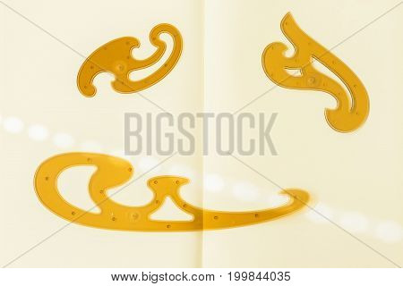 French curve on the paper background, designer's drawing instrument, beige and brown colors. Concept Back to School