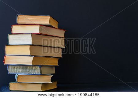 Close-up of a stack of thick books in hard multicolored bindings on a black background. Place for text, the concept of starting school, back to school, education