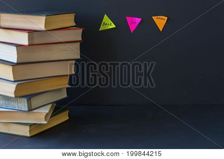 Close-up of a stack of books in hard bindings on a black background. Place for text, concept of starting school, back to school, education