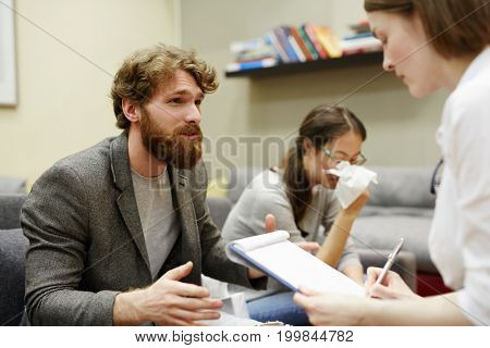 Bearded patient explaining the situation with his wife to counselor