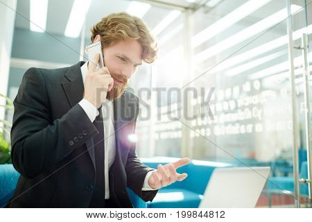 Busy salesman consulting client on the phone in office