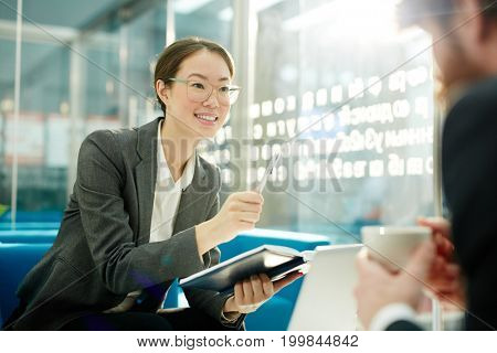 Pretty woman in formalwear discussing plans or project with colleague in office
