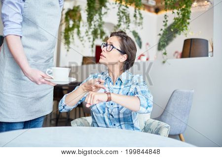 Irritated middle-aged cafe visitor pointing at wristwatch with displeasure while unrecognizable waitress serving coffee
