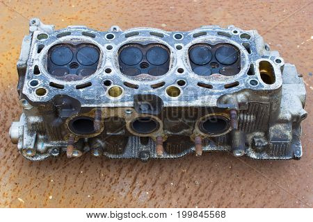 Cylinder head on rusty steell. Horizontal image