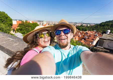 Happy young couple in love takes selfie portrait in Prague, Czech Republic. Pretty tourists make funny photos for travel blog in Europe