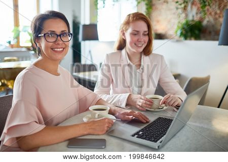 Waist-up portrait of pretty middle-aged businesswoman looking at camera with charming smile while having working meeting at cozy small coffeehouse