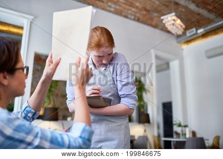 Frightened red-haired waitress standing next to female visitor with pencil and notepad in hands while being criticized in rude manner