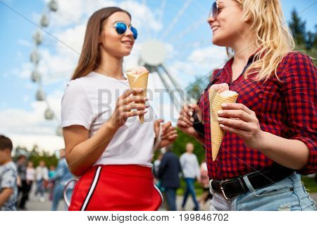 Happy girls with waffled cone ice-cream having nice time in theme park